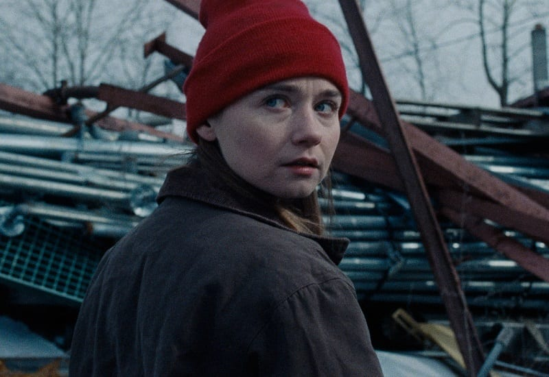 In this image from Nicole Riegel's Holler, the character Ruth (played by Jessica Barden) stands in front of scrap metal and stares at the camera.