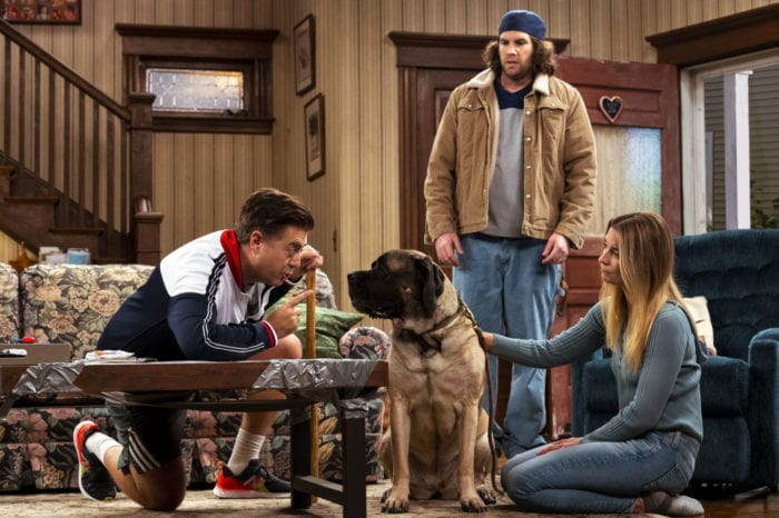 Kevin and Allison talk to a dog while Neil looks on in their sitcom living room.