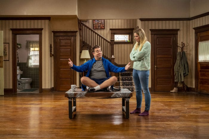 Kevin sits on a coffee table in the middle of an empty room as Allison looks at him with her arms crossed in the sitcom living room.