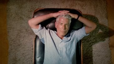 Anthony Bourdain lies down on a couch looking up at the camera with his hands resting on top of his head