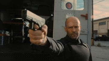 H (Jason Statham) points a gun at the men who are trying to rob his cash truck.