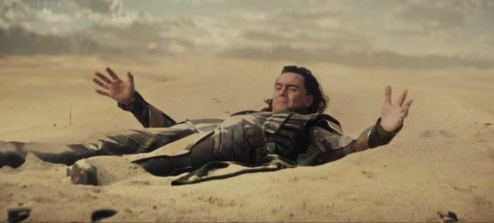 Loki pulls himself out of the sand after crash-landing in the desert.
