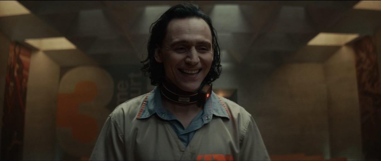 Loki laughs during his trial wearing a prison jumpsuit and a shock collar.