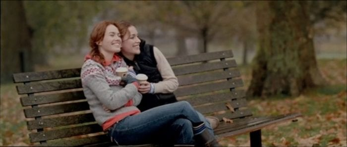 Luce (Lena Headey) and Rachel (Piper Perabo) snuggle close on a bench to keep warm.