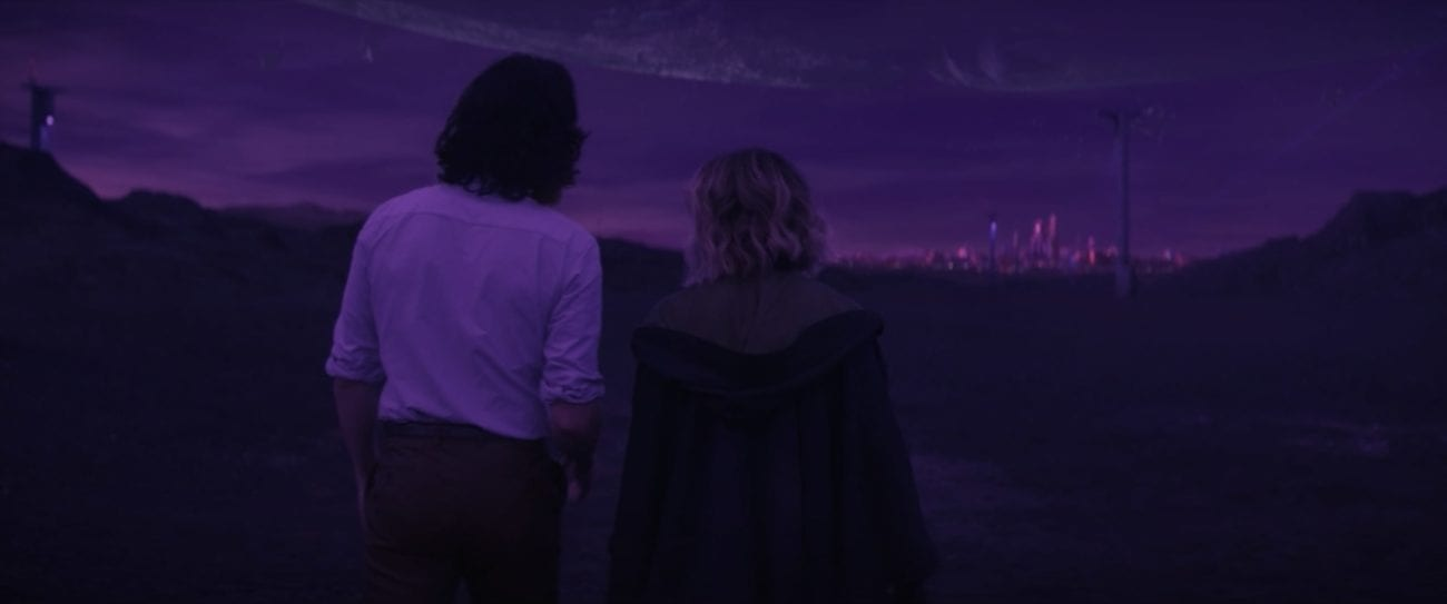 Loki (left) and Sylvie (right) and framed from behind, walking towards a purple skyline.