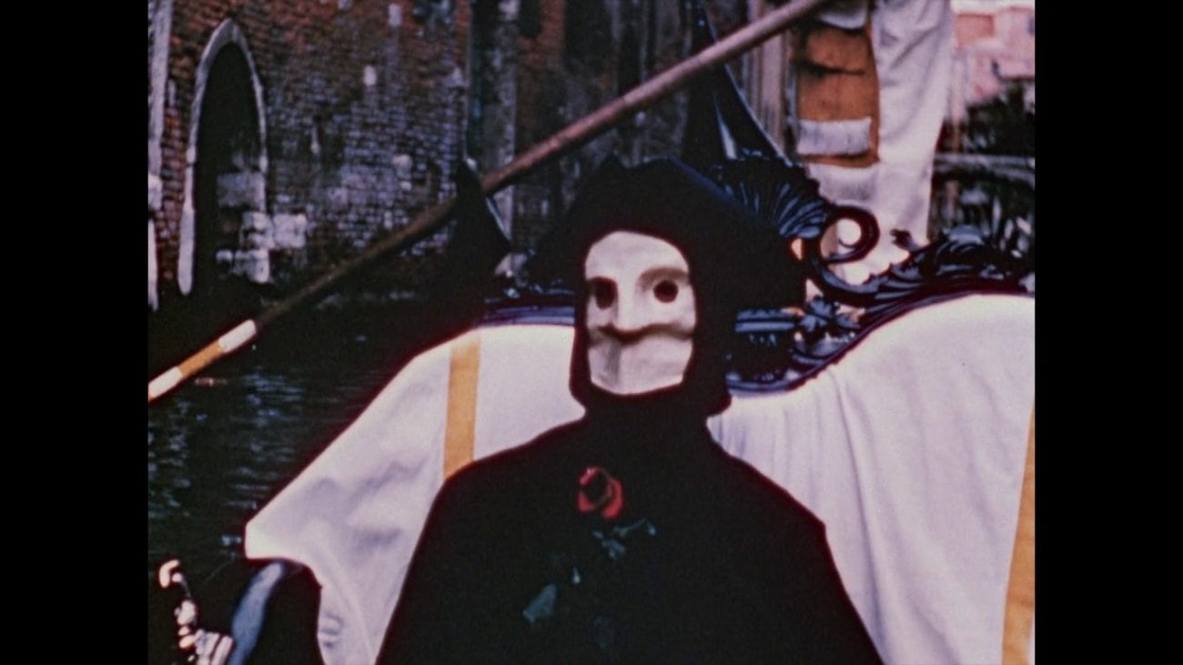 Still from The Assignation. The masked personification of death rides in a gondola in Venice. He is holding a rose.