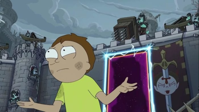 In front of a portal, a frustrated Morty gestures at unseen foes . He is standing in a castle courtyard - on the battlements, large medieval weapons are pointing at him, and a flag displays his head with a knife sticking out