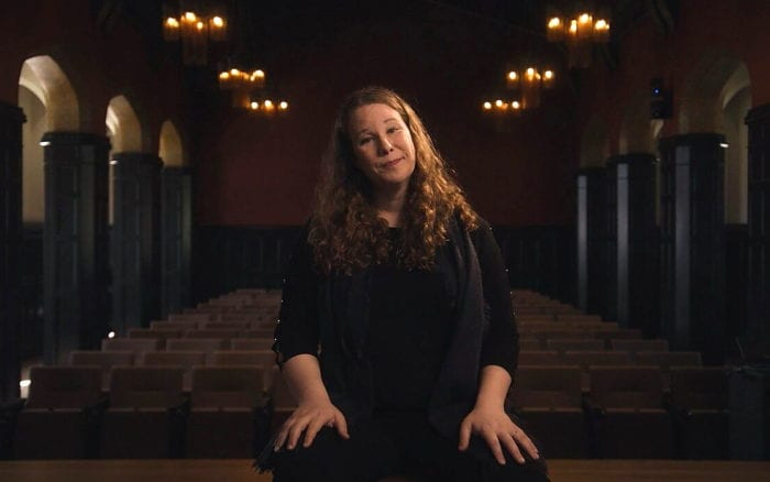 Opera performer Lucia Lucas crouches on a stage in front of rows of empty concert seats