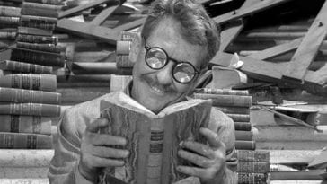 """Still from The Twilight Zone episode """"Time Enough at Last."""" Henry Bemis sits on the steps of the library happily reading a book."""