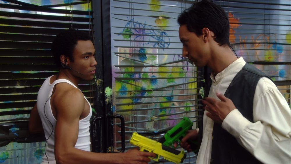 Troy Barnes (Donald Glover) and Abed Nadir (Danny Pudi) do their signature handshake while holding paintball guns in the paint-splattered study room
