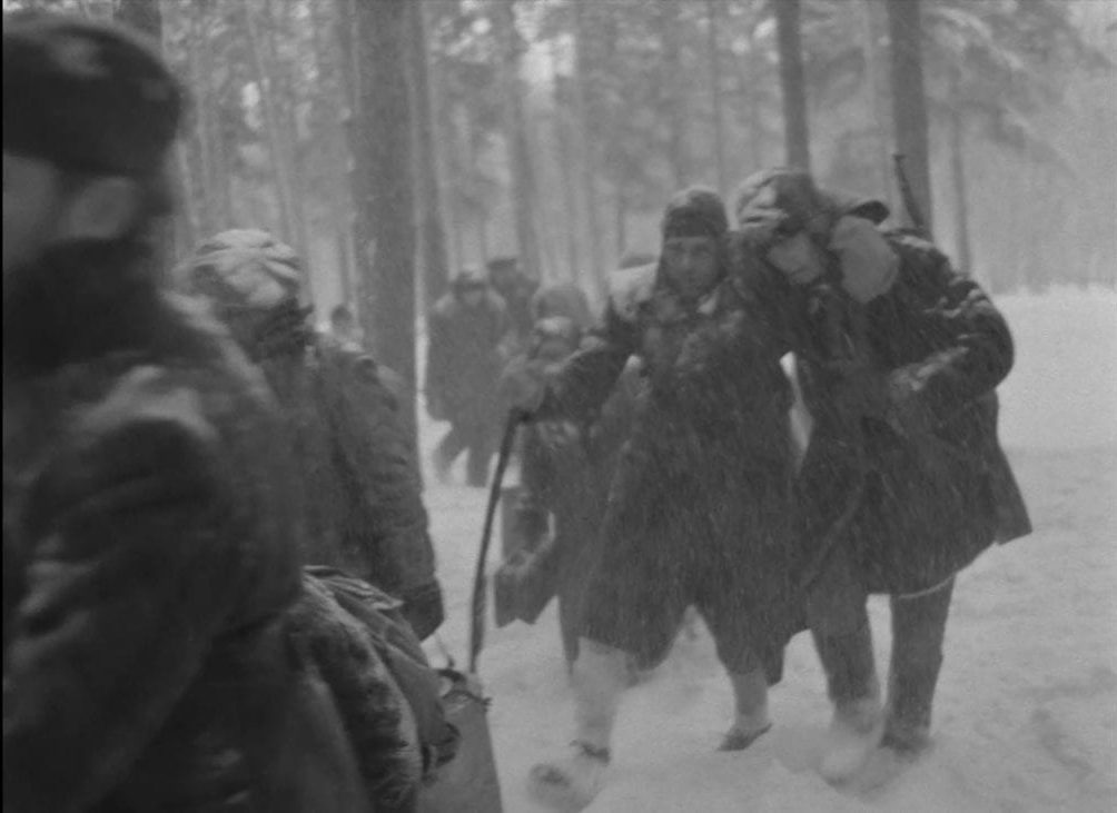 A wounded group of soldiers and villagers are shown in the snowy woods in this image from The Ascent