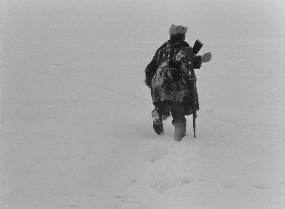 A man in a heavy coat with a rifle trudges through a deep barren snowdrift in this image from The Ascent..