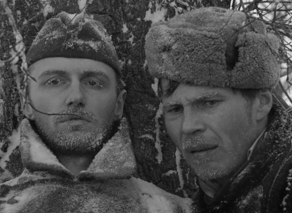 Two Russan soldiers face the camera, their eyelids and facial hair covered in frost in this image from The Ascent.