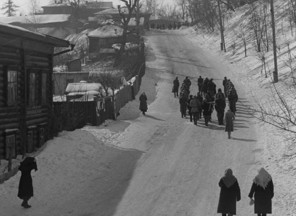 A small group of captive villagers are led up a snowy hill by German soldiers in this image from The Ascent.
