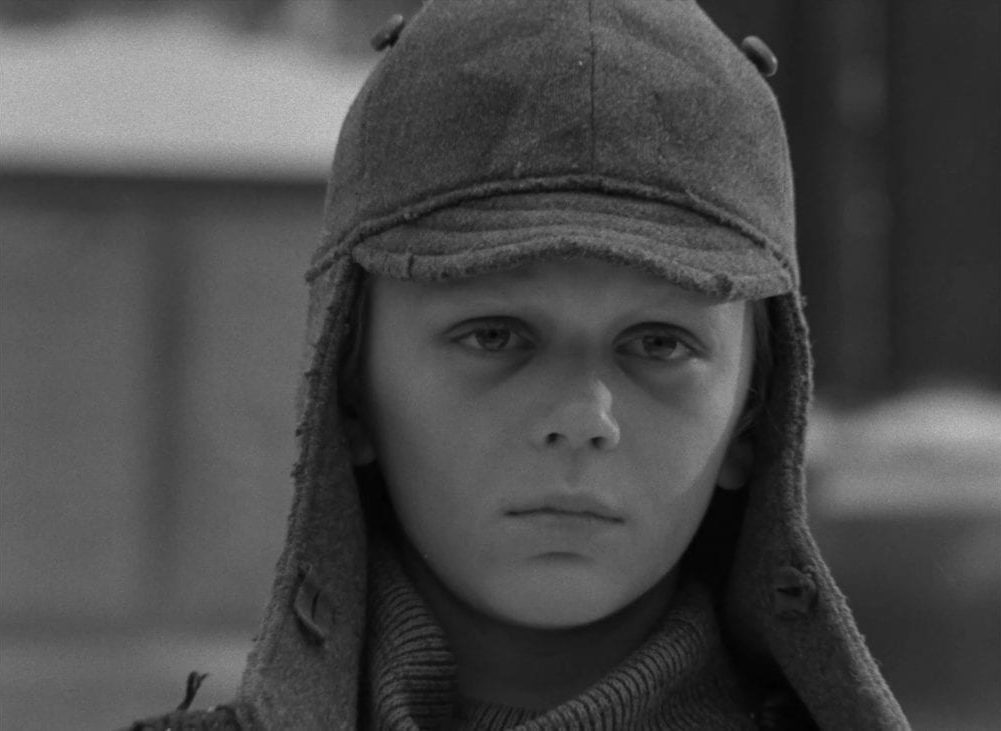 A young boy dressed in a Russian winter cap stares at the camera in this image from The Ascent.
