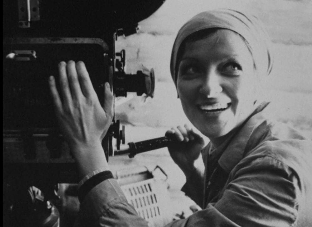 Larisa Shepitko is depicted smiling as she operates a film camera.