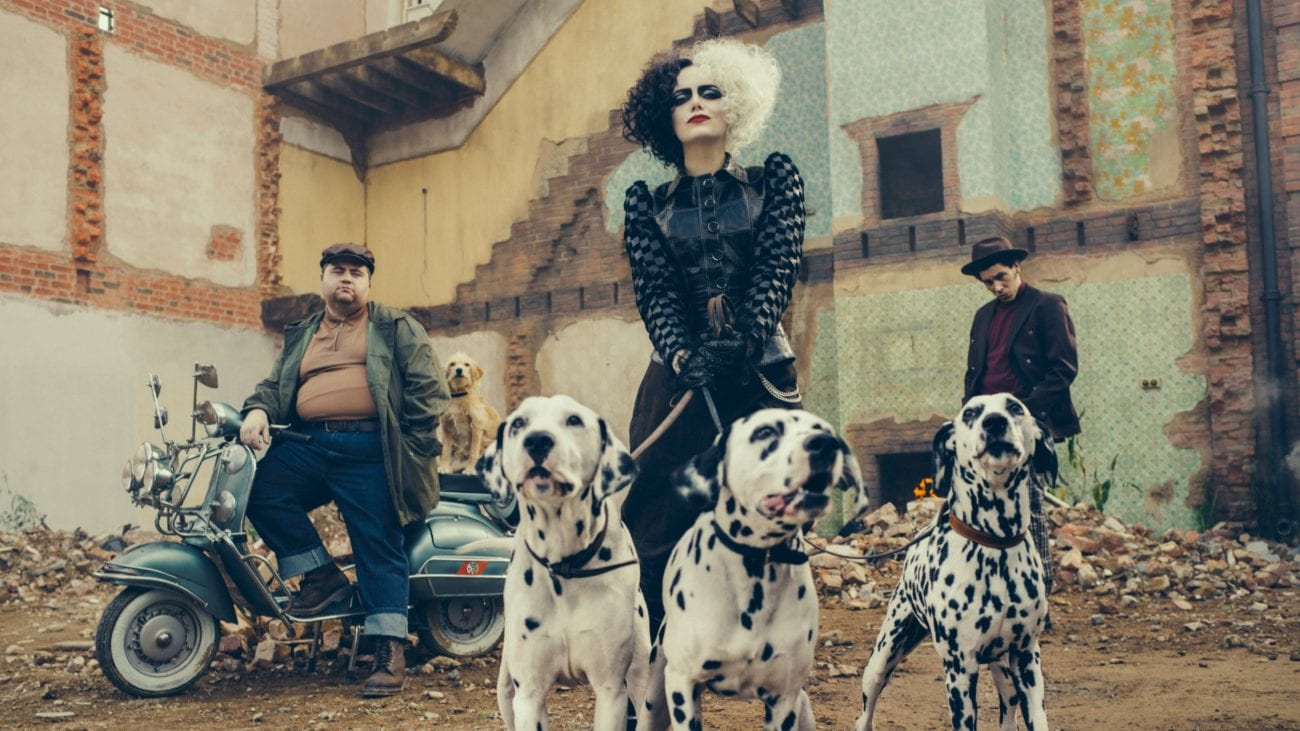 Cruella holds three Dalmatians on a leash while her cohorts stand nearby