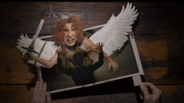 """A hand manipulates a pop-up book of an angel attacking a man in the title card for Evil S2E2 """"A is for Angel"""""""