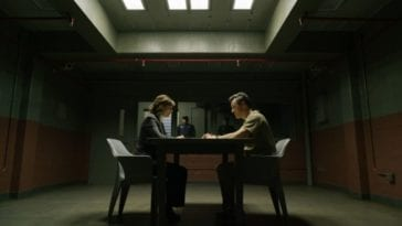 Kristen and a suspect face each other across a table in an interrogation room.