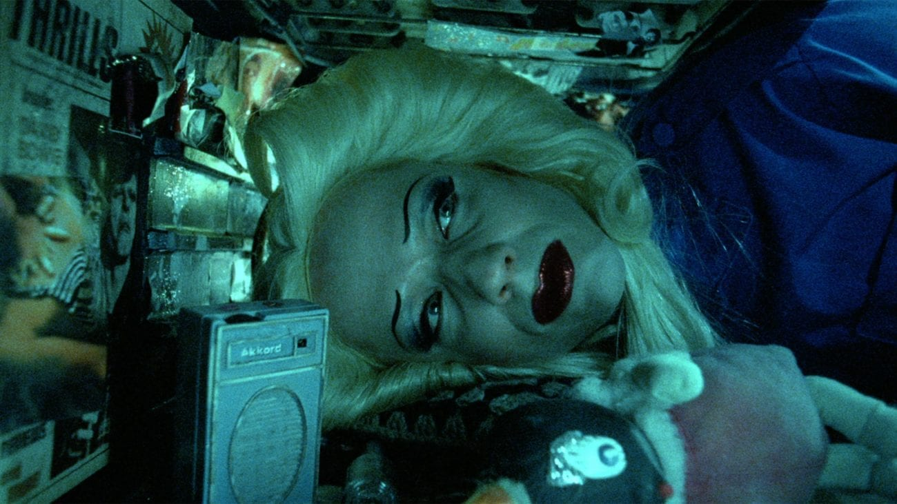 Hedwig (John Cameron Mitchell) lies with their head in the oven as they reminisce on their childhood in Hedwig and the Angry Inch (2001)