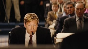 Nick Naylor (Aaron Eckhart) speaks into a microphone in a courtroom full of people in Thank You for Smoking