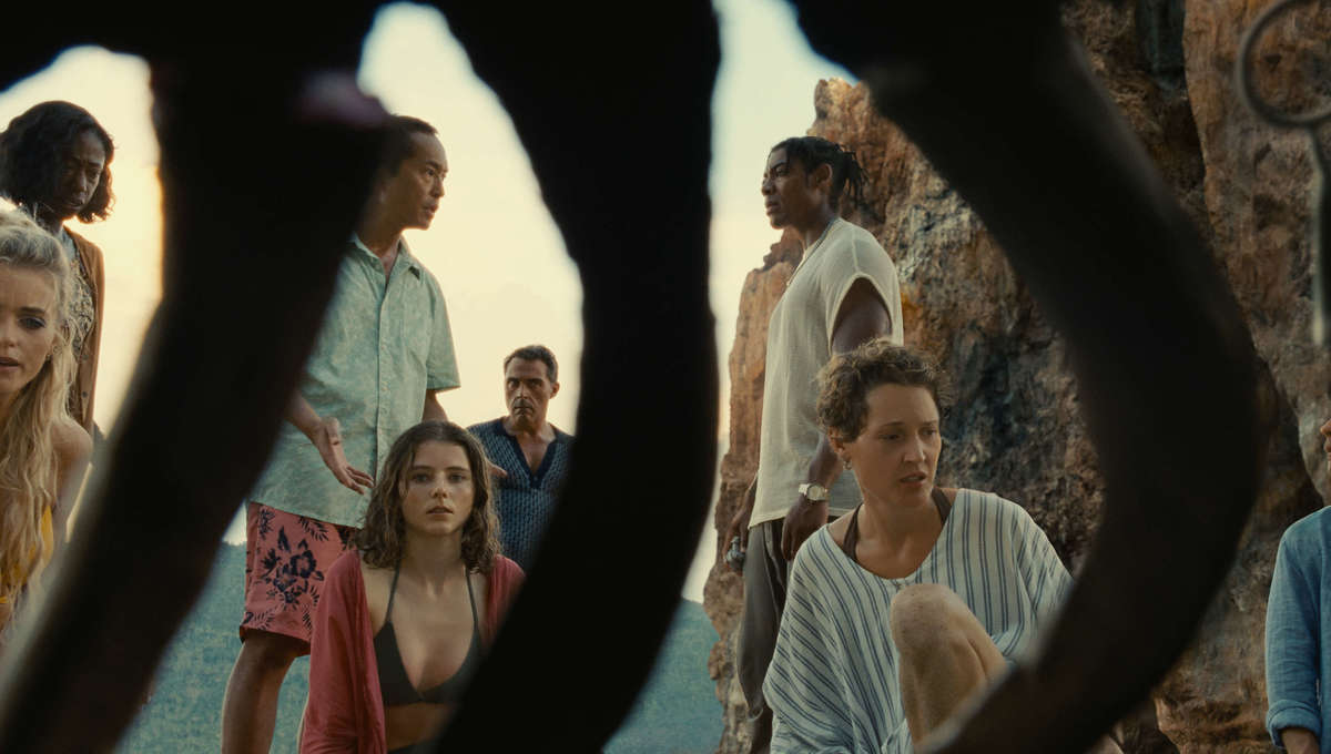 Prisca (Vicky Krieps), Maddox (Thomasin McKenzie), and others on the mysterious island stare in confusion as a dead body has fully decomposed within of few hours.