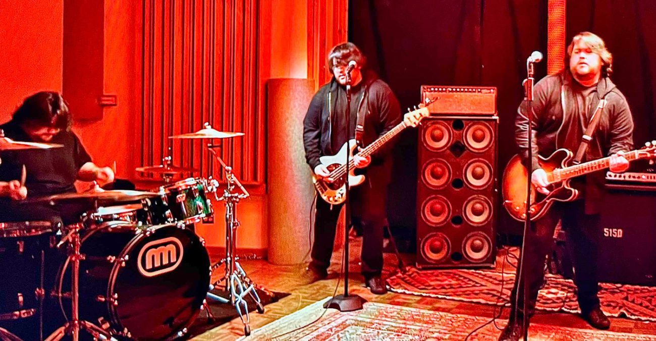 Photoshopped image of Wolfgang Van Halen playing three different instruments as if there were three of him in the band.