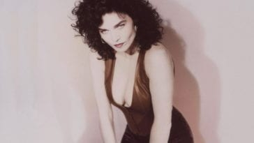 Alannah Myles poses in a red leather bustier and velvet skirt agin front of a light purple wall