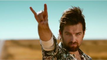 Antony Starr holds his right hand up with his first finger and pinky finger extended like horns while a bright desert background lays behind him