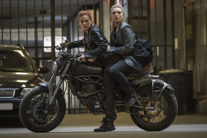 Yelena and Natasha stop after a turn on a motorcycle.