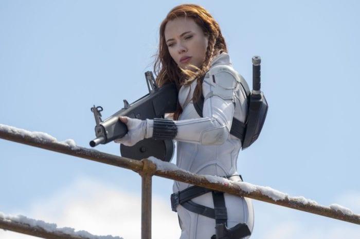 Natasha aims her rifle down as pursuing guards.