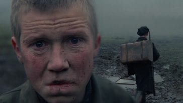 In this image from Come and See, the character Flyora, aged by his experience, stares in angusih at the camera while a young boy behind him carries a rifle and pack.