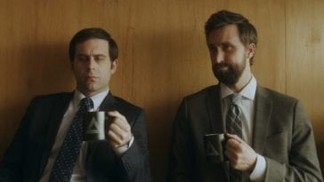 Two men hold coffee mugs and make faces in Comedy Central's Corporate
