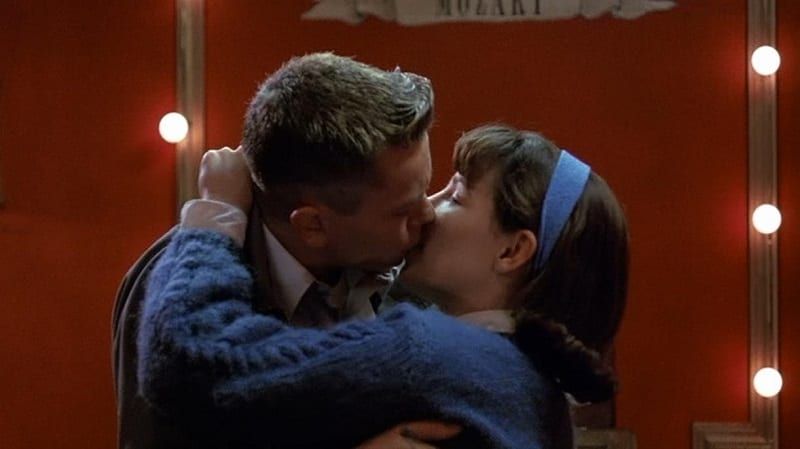 In this image from Dogfight, Eddie (River Phoenix) and Rose (Lili Taylor) embrace and kiss in front of a red backdrop.
