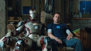 Tony Stark sits on a couch next to his disabled Iron Man armor