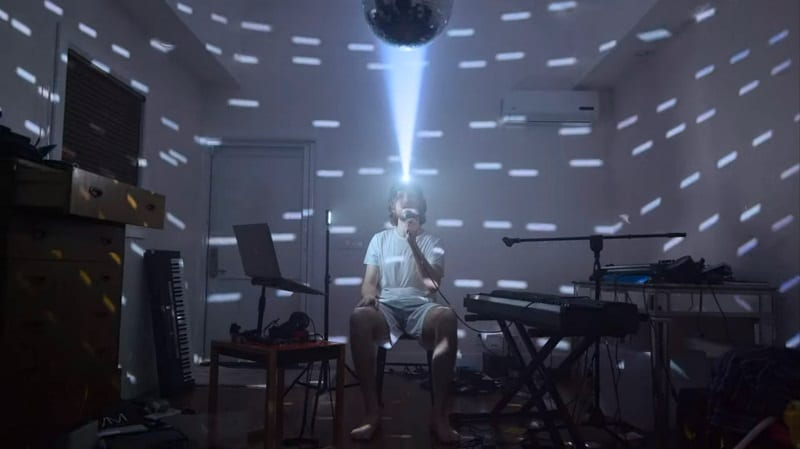 In this image from Inside, Bo Burnham is depicted alone in a room, a headlamp aimed at a mirrored ball creating a lightshow.