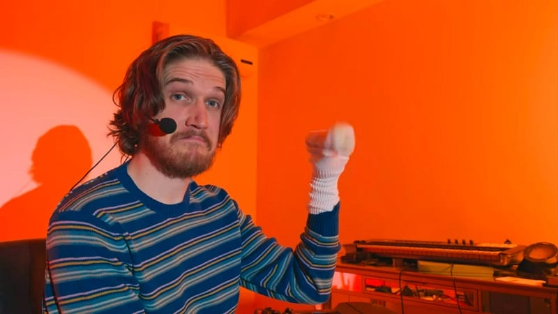 In this image from Inside, Bo Burnham is depicted holding a sockpuppet in front of an orange background.