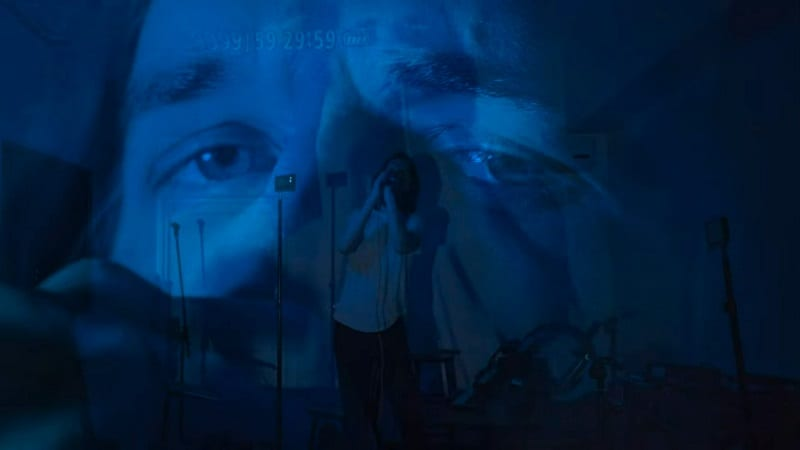 """In this image from Inside, a triple exposure of Bo Burnham depicts multiple blue-tinted images of the singer performing """"Goodbye""""."""