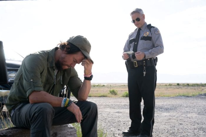 Joe sits in lament in talking with a standing sheriff.