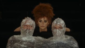 Oliver Martinez (left) and Antonio Banderas (right) sit in theater seats covered in bubble wrap; only their eyes can be seen. Penélope Cruz stands behind them.