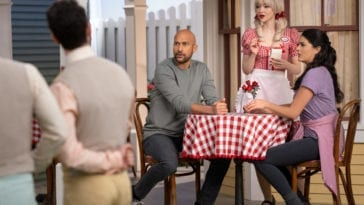 Josh (Keegan-Michael Key) and Mel (Cecily Strong) sit at a table with a checkered table cloth being served by Betsy (Dove Cameron) as Schmigadoon! residents sing in front of them