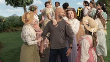 Josh (Keegan-Michael Key) stands at the center of a large group of women from Schmigadoon in front of the cartoonish tree lined background