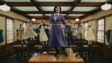 Miss Emma Tate (Ariana DeBose) standing on a desk in a schoolroom, holding a cane and looking forward while the students stand on desks behind her, all of them are tap dancing