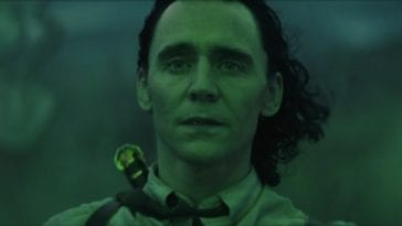 Loki looks at his first successful enchantment, bathed in green light.