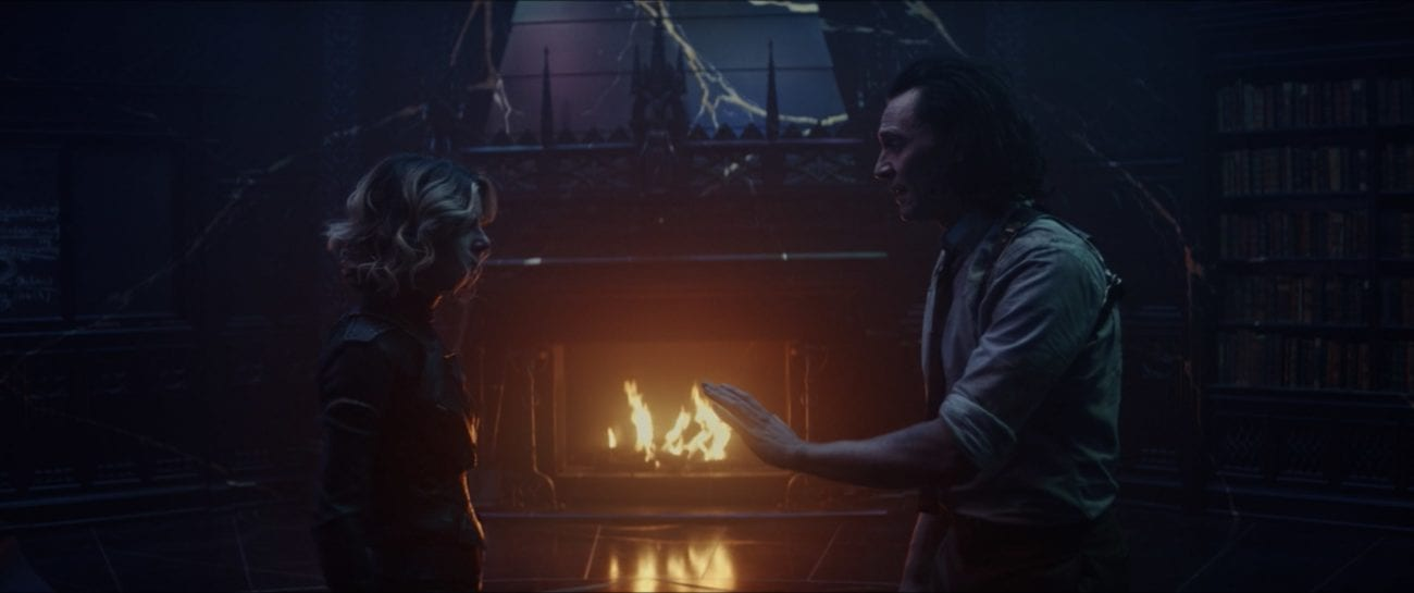 Loki (right) extends his hand to Sylvie (left) as they stand in front of a fireplace, about to fight.
