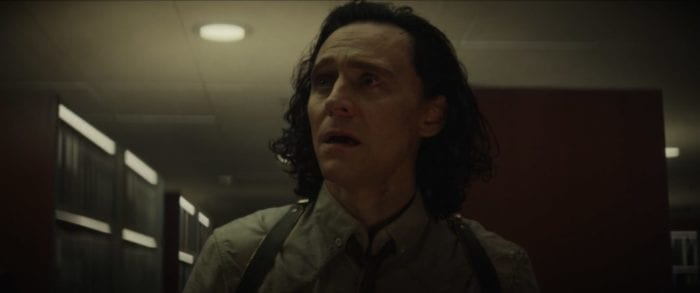 Loki stands center and looks offscreen with a horrified expression.