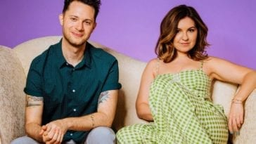 Tova Litvin and DougRockwell sit together on a couch in front of a purple wall