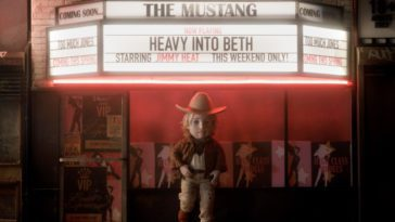 Street Hustler Boy stands outside of a theater with a marquee in the background that says Heavy into Beth