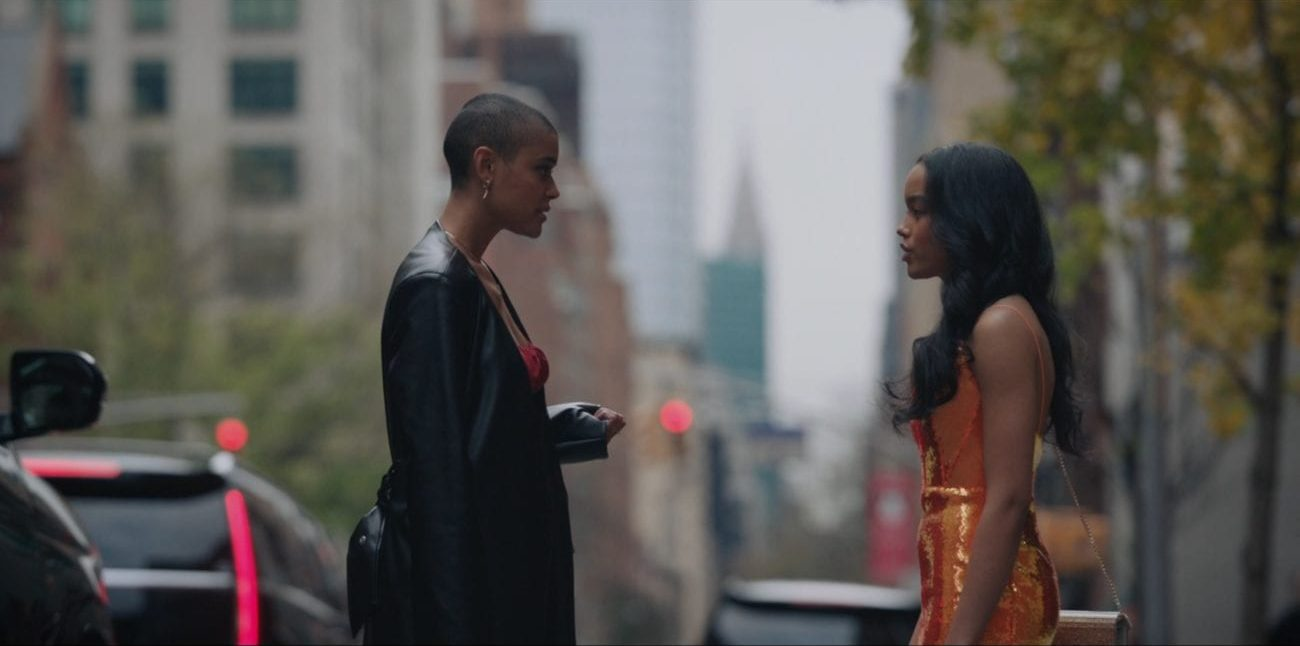 Julien (left) and Zoya (right) standing on a sidewalk on an overcast day. Julien is wearing a red dress covered by a heavy leather coat and has one some gold earrings. Her left arm is facing upward and her fingers are clutched. Zoya is wearing a vibrant sequined orange dress and carrying a sparkling gold purse hung around her shoulder by a gold chain. Her hair is styled with gentle waves. The two are talking and are displeased with one another.