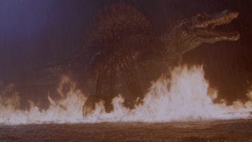 Spinosaurus walks in a lake that is on fire in jurassic park 3